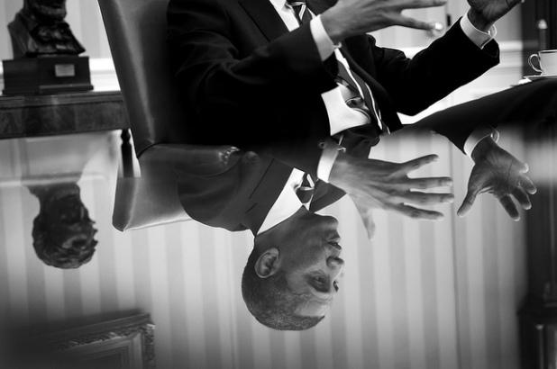 El Presidente se refleja en el vidrio de la mesa del despacho Oval. Créditos: Pete Souza