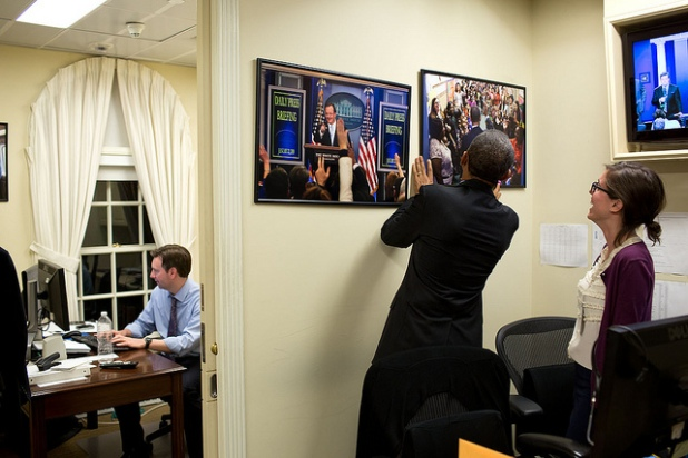 Barack Obama coloca las fotografías que están torcidas en primer plano y en segundo plano el secretario de prensa trabajando. Créditos: Pete Souza