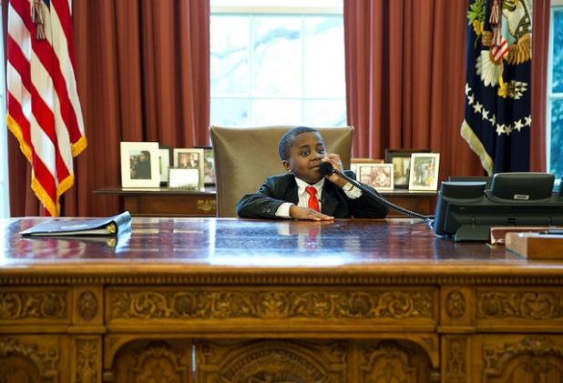 Robby Novak, 'Kid Presidente', finge una llamada de teléfono en el despacho oval. Crédito: Pete Souza